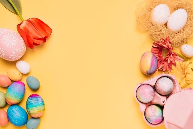 신선한 튤립의 오버 헤드보기; 거 베라와 노란색 표면에 다채로운 부활절 달걀
