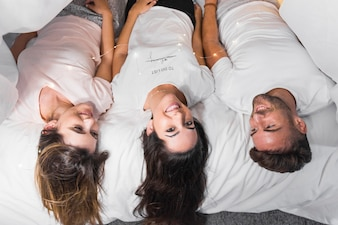 An overhead view of friends lying on bed with ferry light over their body
