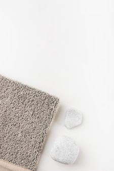 An overhead view of gray loofah with spa stone