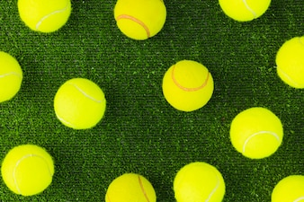 An overhead view of green tennis balls on turf