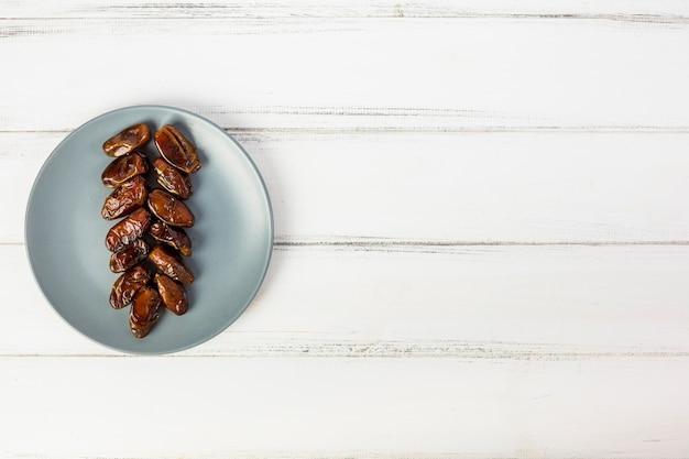 Вид сверху на серую тарелку с аранжированными сочными финиками на белом деревянном столе