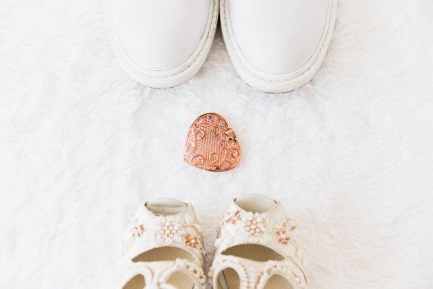 An overhead view of groom shoes and bride sandal on white fur