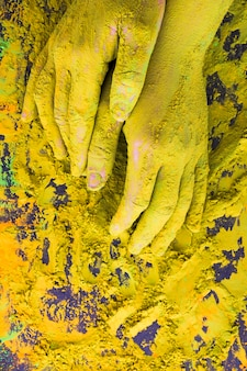 An overhead view of hand covered with yellow powder paint