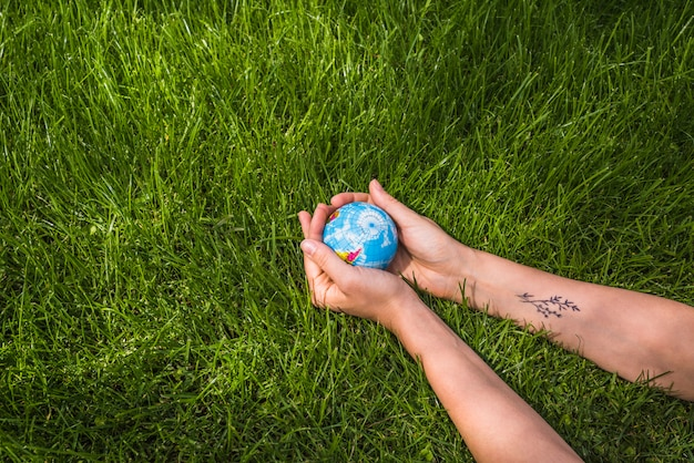 Вид сверху руки, держа глобус мяч на зеленой траве