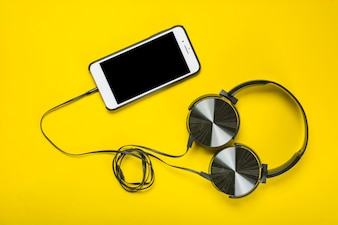 An overhead view of headphone attached with cellphone on yellow background
