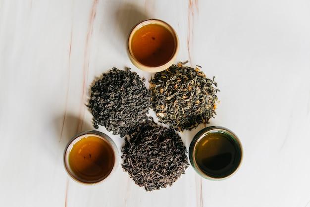 Вид сверху на травяные чашки с разнообразием сухих чайных листьев на мраморном фоне