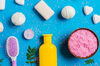 An overhead view of himalayan salt; soap and hairbrush on blue background