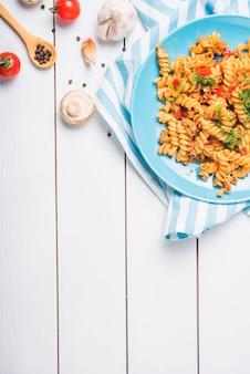 Верхний вид домашней фузилли макароны с ингредиентами на деревянном столе