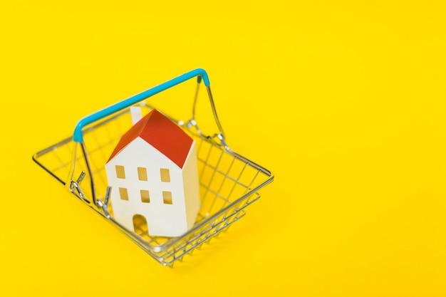 노란색 배경에 쇼핑 카트 안에 집 모델의 오버 헤드보기