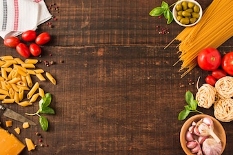 An overhead view of ingredients for making italian pasta on wooden background