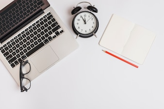 An overhead view of laptop; alarm clock; pencil; notebook and eyeglasses on white background