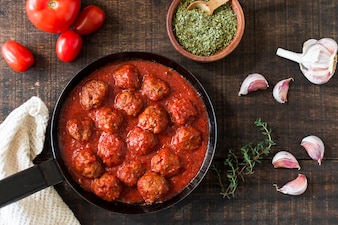 An overhead view of meatballs in sweet and sour tomato sauce with ingredients