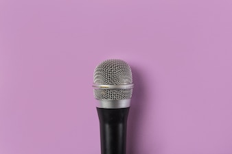 An overhead view of microphone on pink background