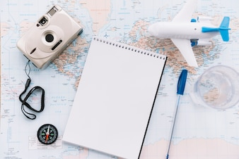 An overhead view of miniature white airplane; spiral blank notepad; pen; camera and compass on map