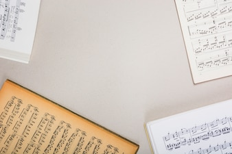 An overhead view of musical note books on white background with space for text