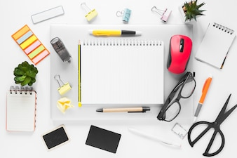 An overhead view of office stationeries on laptop over white background