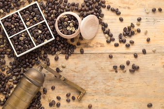 An overhead view of old coffee grinder with coffee beans in container and table