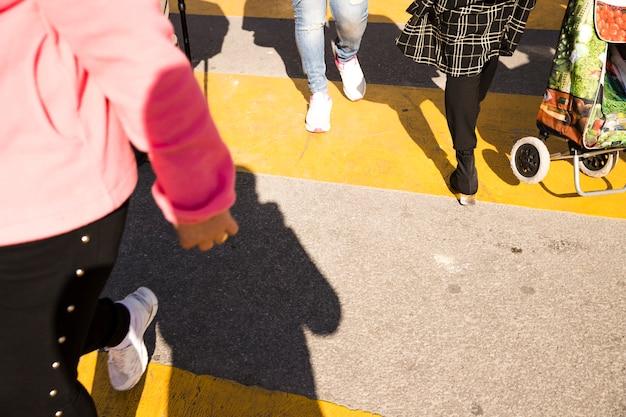 Вид сверху людей, пересекающих по желтому асфальту пешеходного перехода