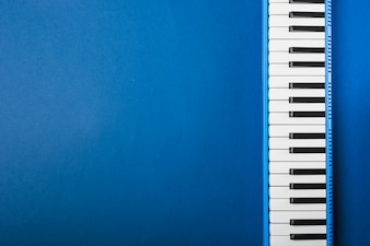 An overhead view of piano keyboard on blue background