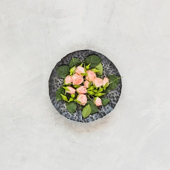 An overhead view of pink flowers on stone tray against concrete backdrop