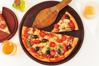 An overhead view of pizza on wooden board with spatula