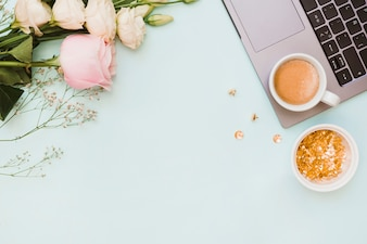 An overhead view of pushpin bowl; coffee cup; flowers and laptop on colored background