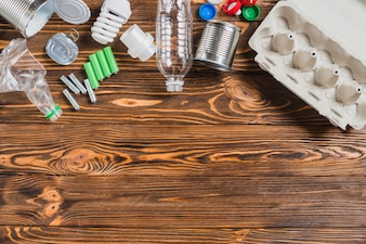 An overhead view of recycle items on brown wooden background