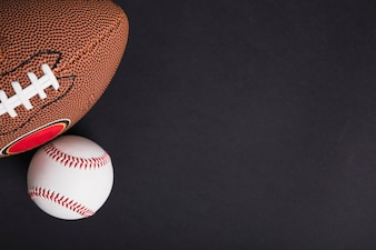 An overhead view of rugby ball and baseball on black background