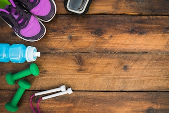 An overhead view of shoes; dumbbells; skipping rope; water bottles on wooden table