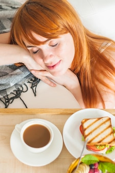 An overhead view of smiling woman resting near the breakfast on wooden tray