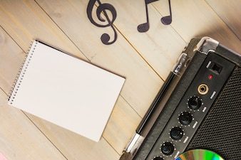 An overhead view of spiral notepad; musical note and amplifier on wooden desk