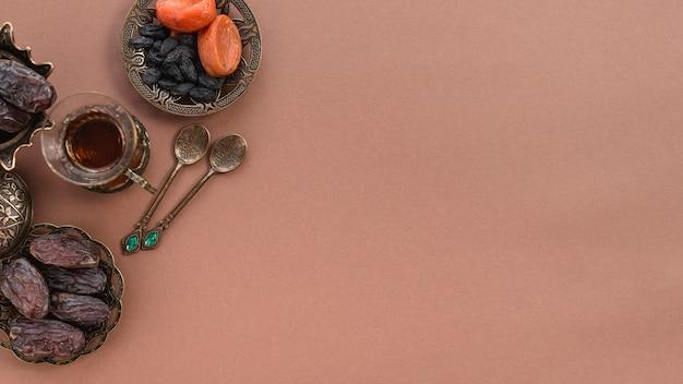 ティーグラスの俯瞰。ドライフルーツ;茶色の背景に日付と金属のスプーン