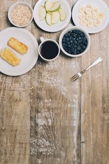 トーストの俯瞰。オーツ麦;ブルーベリー;コーヒーカップ;テーブルの上のリンゴとバナナのスライス