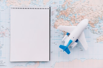 An overhead view of toy white airplane and spiral blank notepad on map