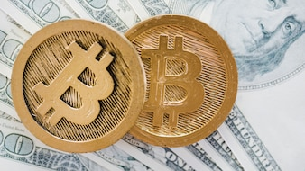 An overhead view of two bitcoins over the spread us dollar notes
