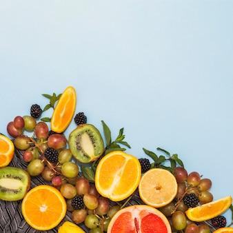 青い背景に様々な半分の果物やブドウのオーバーヘッドビュー