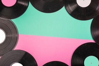 An overhead view of vinyl records border on dual green and pink background