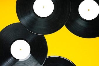 An overhead view of vinyl records on yellow background