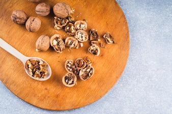 An overhead view of walnuts on wooden chopping board