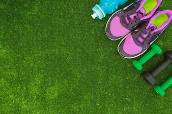 An overhead view of water bottle; sport shoes and dumbbells on green turf