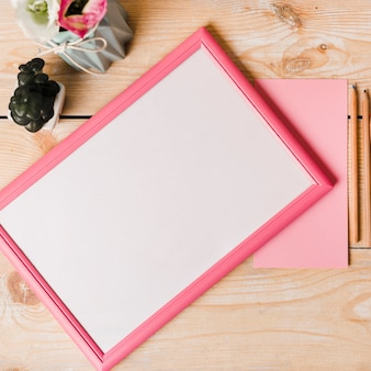 An overhead view of white blank frame with pink border; paper; colored pencils and vase on wooden desk