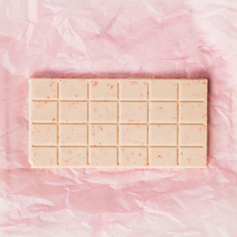 An overhead view of white chocolate bar on pink paper wrapper