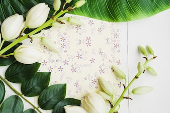 An overhead view of white flower twig on floral paper over the wooden backdrop