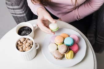 An overhead view of woman holding macaroon with cup of brown sugar cubes and coffee on white table