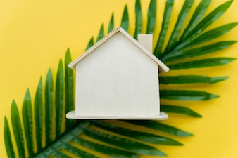 An overhead view of wooden house over the green leaves against yellow background