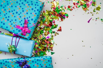 An overhead view of wrapped gift boxes with colorful confetti on gray background