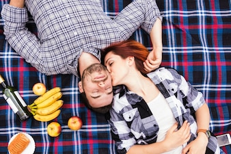 An overhead view of young woman kissing her boyfriend lying on blanket