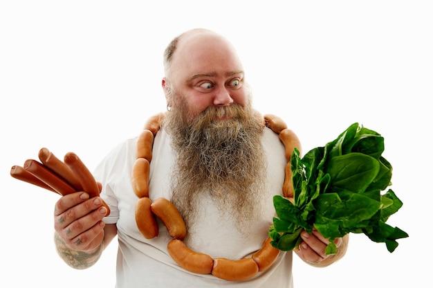 Мужчина с большим весом, с кучей сосисок на шее, смотрит на шпинат и с другой стороны держит сосиски, пытаясь выбрать, что полезнее