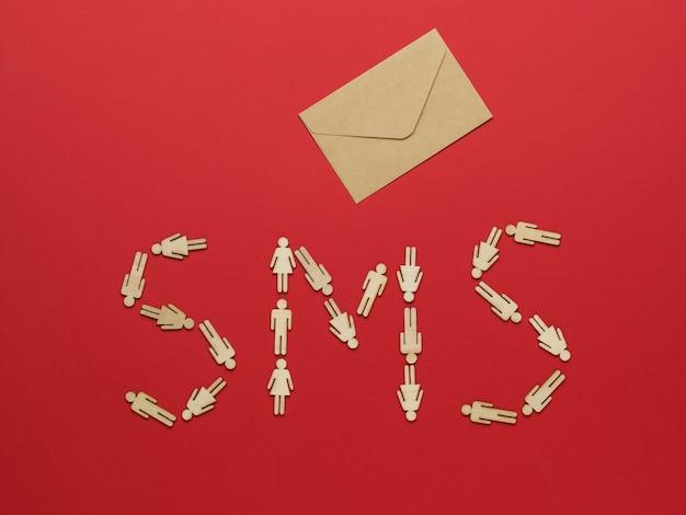 Sms-надпись из фигурок человечков и почтового конверта на красном фоне. концепция общения между людьми.