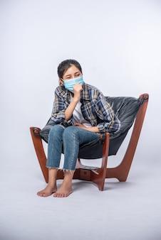 椅子に座ってマスクをかぶった不快な女性